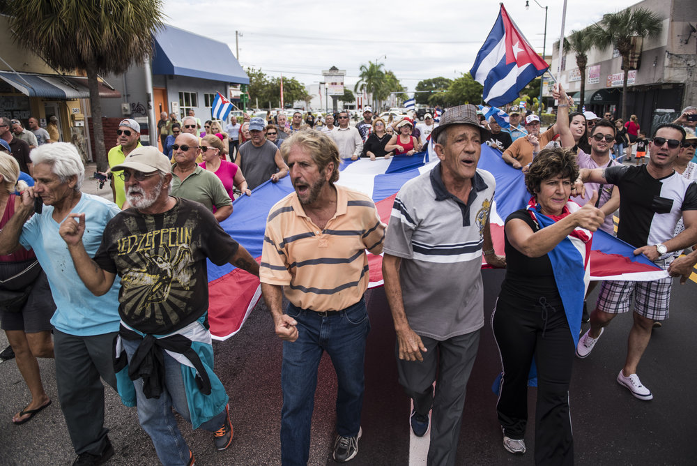 "One of the Cuban exile's most outspoken advocate and leader of ""Vigilia Mambisa,"" Miguel Saavedra, marches down the street with a group while carrying the Cuban flag."