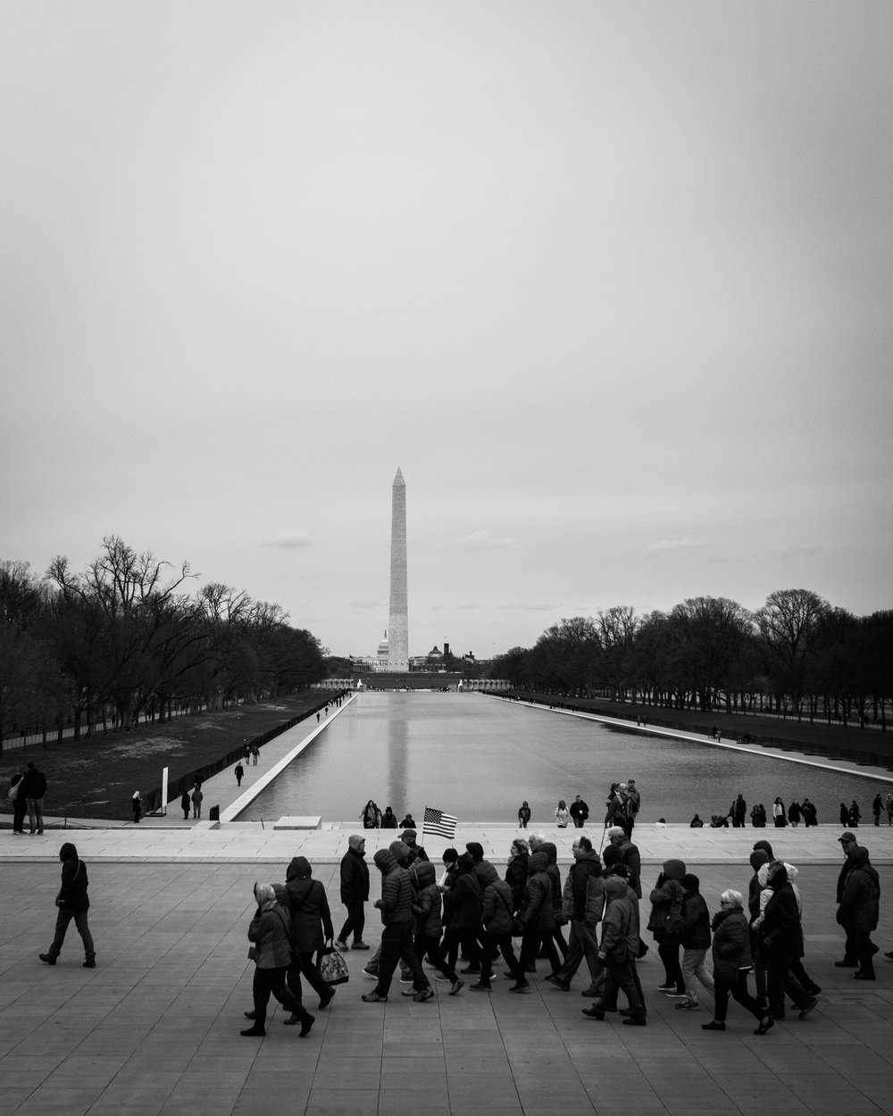 A group of tourists walks in front of the Lincoln Memorial Reflecting Pool.