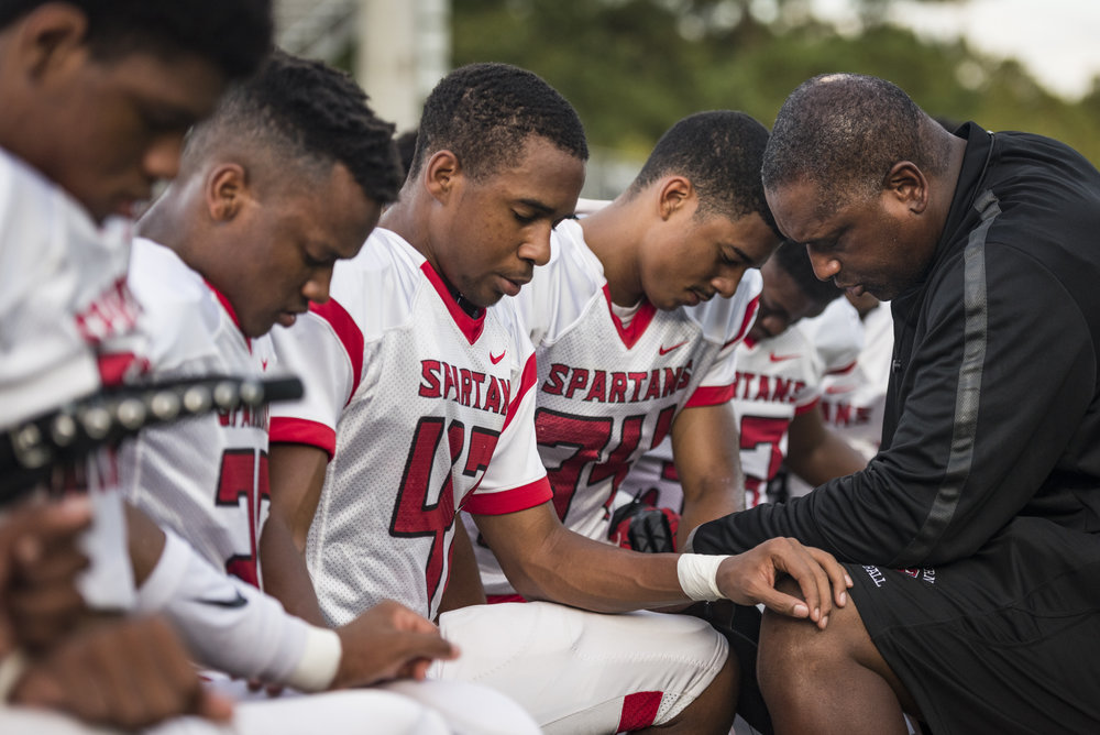 "Southern Spartan head coach Darius Robinson prays with his players before the team's game against Cardinal Gibbons. During a pre-game pep talk with his players, Head Coach Robinson asked his players if they knew why they prayed... ""We pray before games because of all the sins we are about to commit on this field."""