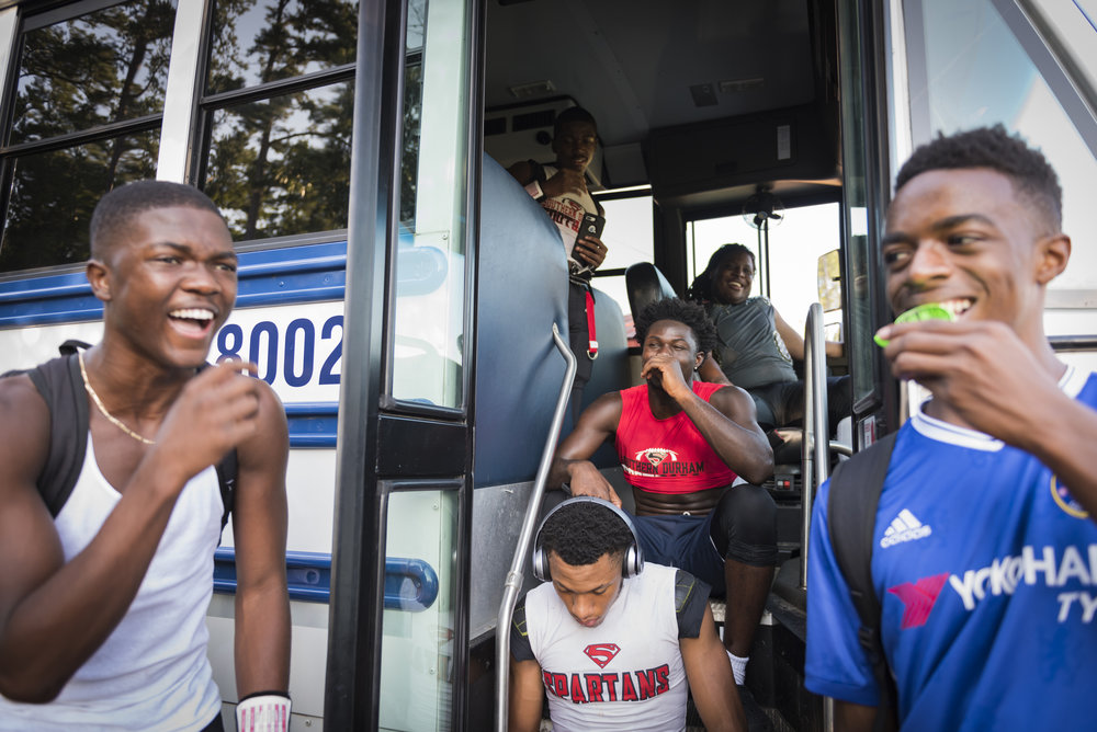 Southern Durham football players relax before an away game. The Spartans usually stayed on the team bus until they had to start warming up. Many schools in the area did not have visitor locker rooms.