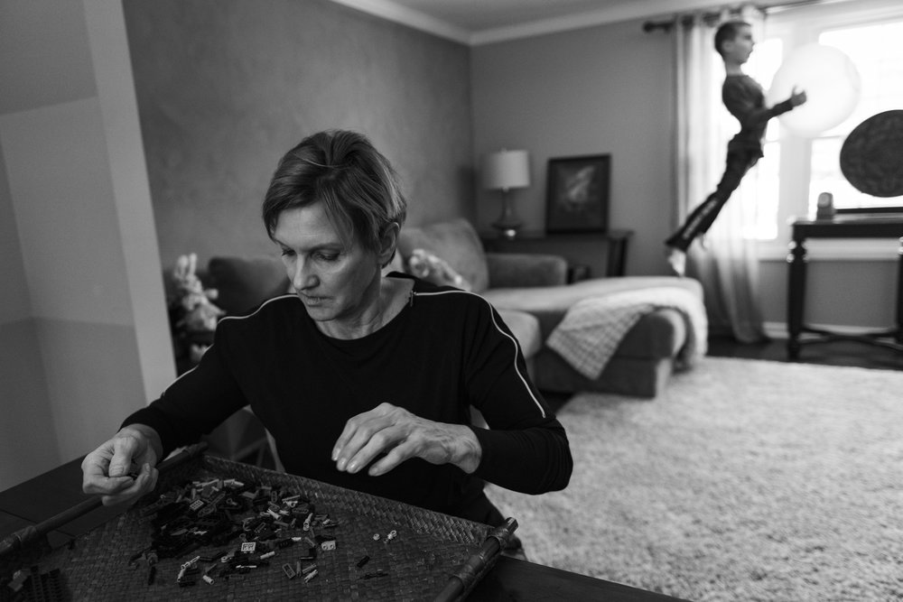 Cretaro organizes her 6-year-old grandson's Legos as he plays in the background. The sorting acts as a home physical therapy for the muscles in her hands.