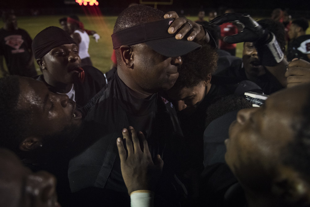 Southern Spartans head coach Darius Robinson celebrates with his players after an  upset win  against the No. 4 team in the region, Seventy-First High School.