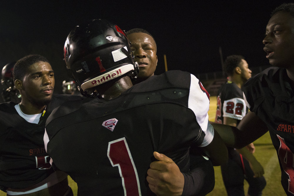 Southern Durham senior wide receiver Jaylen Lloyd is consoled by senior running back Taron Beauford (1) and teammates after a tough loss.