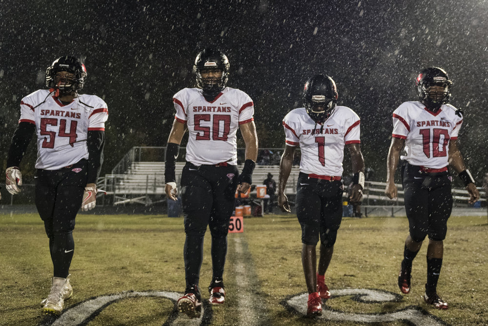 Southern Durham senior captains walk to the center of the field for the coin toss. The Spartans won their second-to-last game against East Chapel Hill, 42-7.