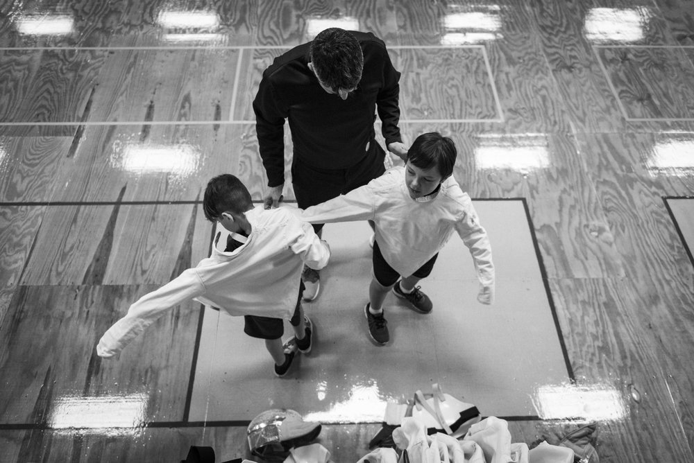 Fencing Coach Jeff Kallio helps two beginning fencing students pick out the right fencing jacket for their first practice at the Mid-South Fencer's Club in Durham, NC.