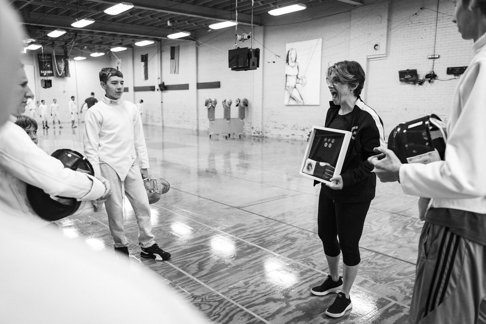 Fencing Coach Jennifer Oldham shows her students the various honors they can receive throughout their fencing career at the Mid-South Fencer's Club.