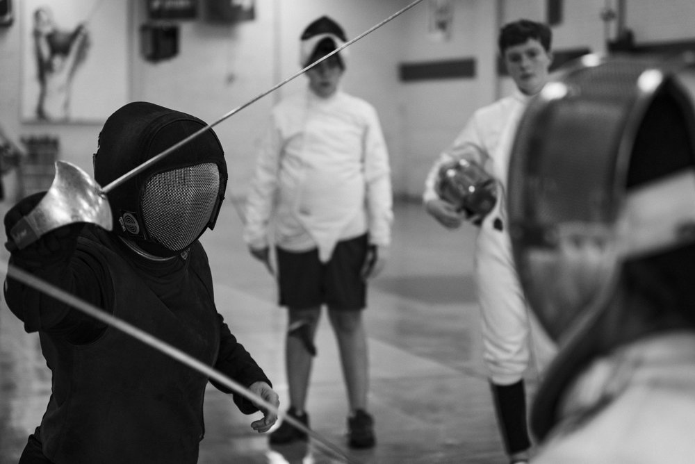 "Fencing Coach Jennifer Oldham shows her students the technique they'll be practicing during the session at the Mid-South Fencer's Club in Durham, NC. Coach Oldham has had an illustrious career both as a fencer and a coach. She holds the title of ""Maitre D'Armes,"" which is conferred by the United States Fencing Coaches Association and certifies her as a qualified fencing coach. Only five people in the state of North Carolina currently hold such title."