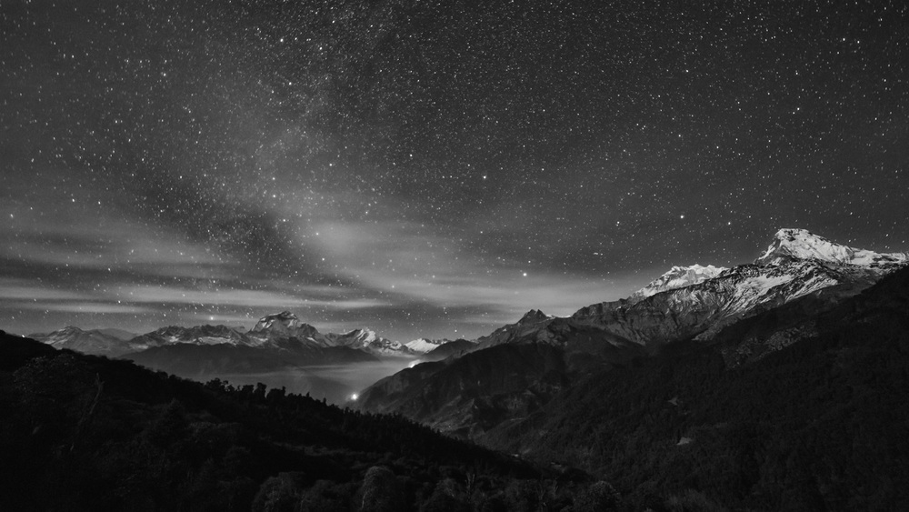 On my way through the Annapurna region (Nepal) I came across this view of Annapurna South. I couldn't see much at the beginning but I could hear how the wind was howling through the valley. After my eyes got used to the darkness I saw stars, mountains lit by moonlight, a forest fire in the distance and between all that the moving clouds. Everything was bound together by the cold air that surrounded me.