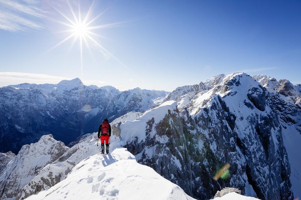 Džani si ogleduje mesto nadaljevanja in stoji na 1 cm snega na skalnatih ploščah.