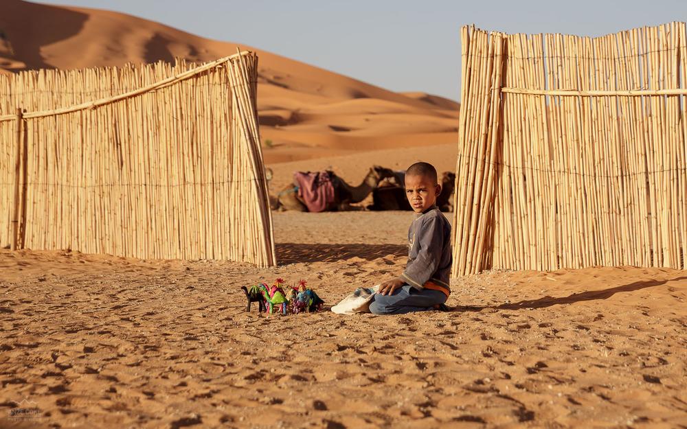 Mlad fant se igra na puščavskem pesku kmalu po sončnem vzhodu.