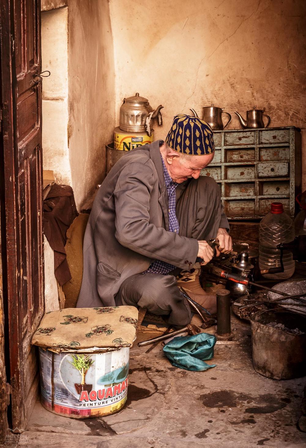 Starejši obrtnik v svoji delavnici.