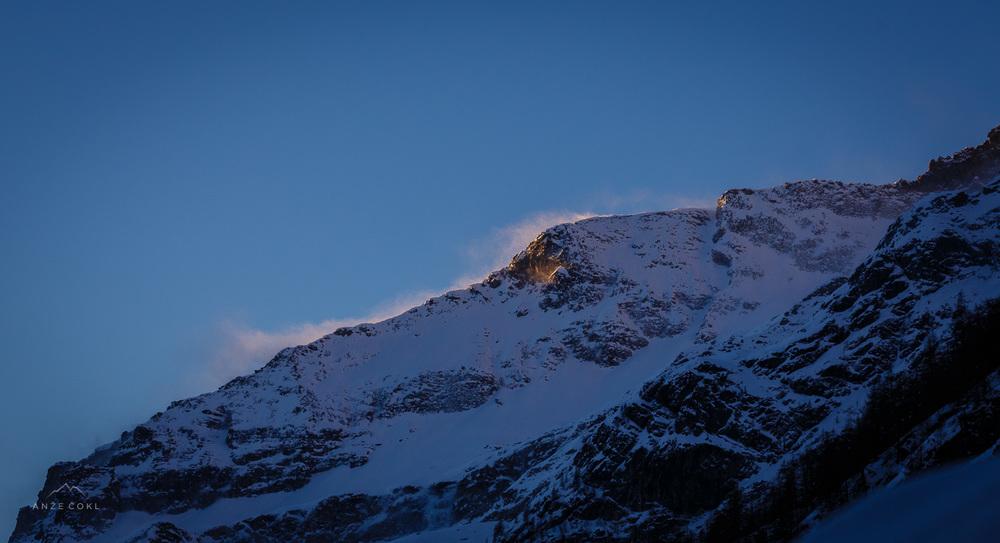 Sončno vzhod in zastave na grebenu napovedujejo vetroven dan.