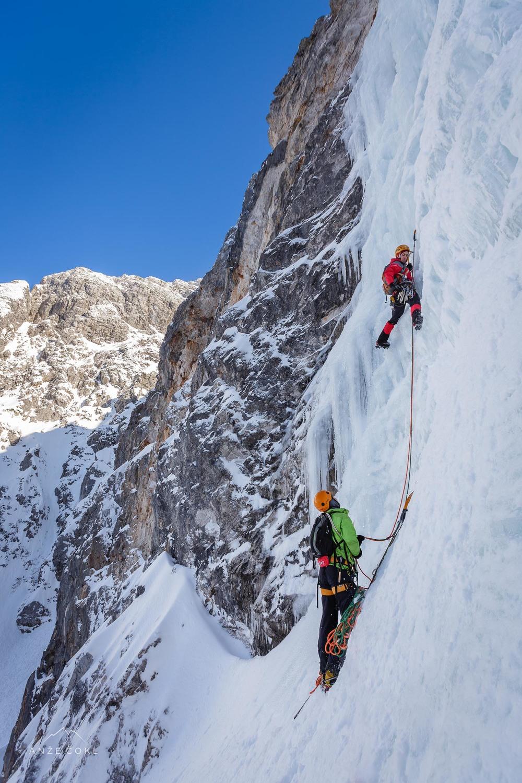 Marko je uvija ledni vijak ob plezanju najtežjega raztežaja, Matevž varuje.