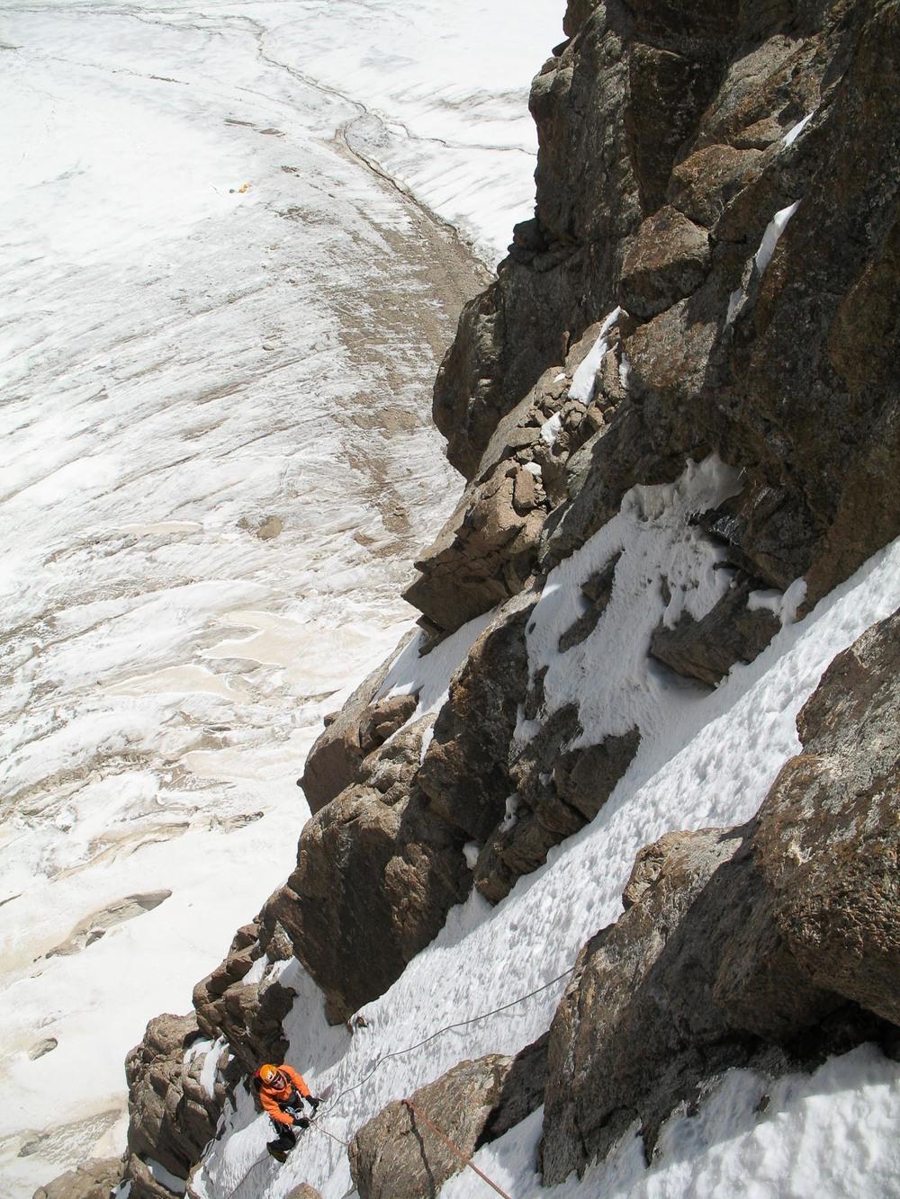 Pogled z varovališča na Arneta, ki pleza prve metre nove smeri na neosvojen vrh Pik Anin.
