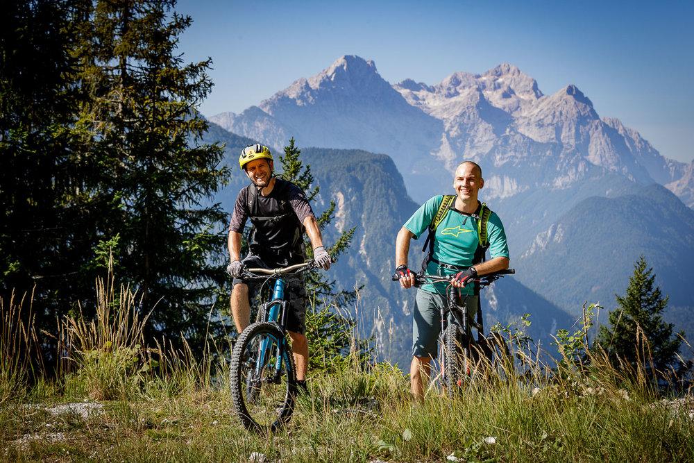 Kolesarja s kuliso Julijskih Alp in Triglavom vred.