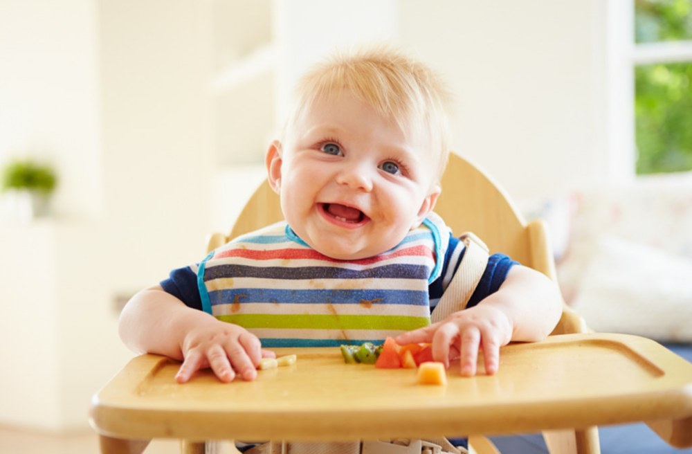 Introducing solids to a baby. baby eating fresh fruit and vegetables.