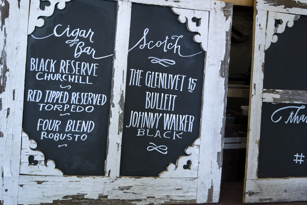 Hand drawn chalkboard signage for what looks to be a tasty cigar and scotch bar for a weekend wedding organized by Shay Brown Events.