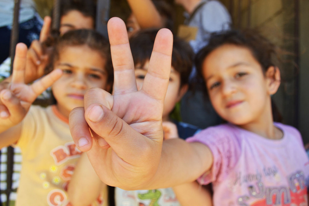 Refugee children (one giving peace sign)