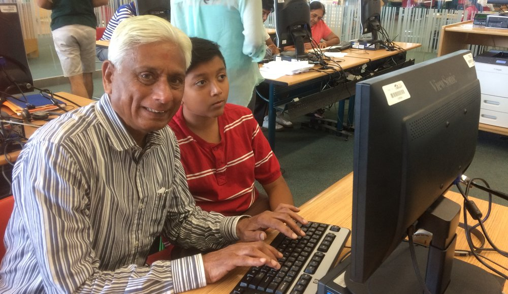 Senior and youth working on a computer