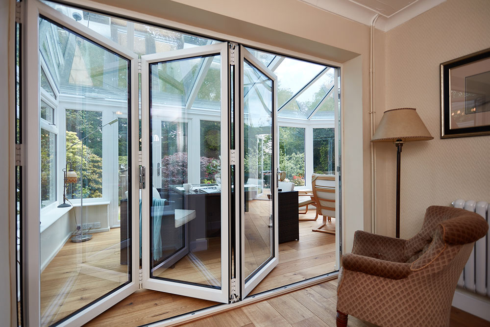 white bifold doors leading in to a upvc conservatory Matson4186.jpg