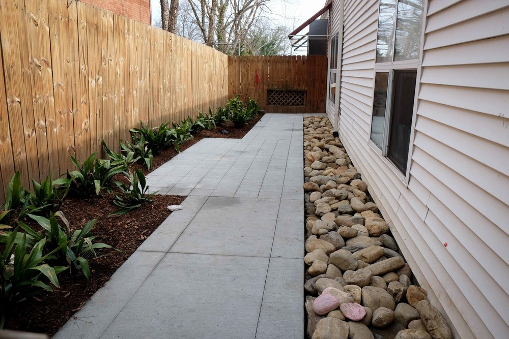 "This was a badly underutilized space with poor drainage. There is a drain line under the stones and the patio is simply scored concrete. It's an ""extra"" space with a low budget that will have a few chairs and a bistro table or two."