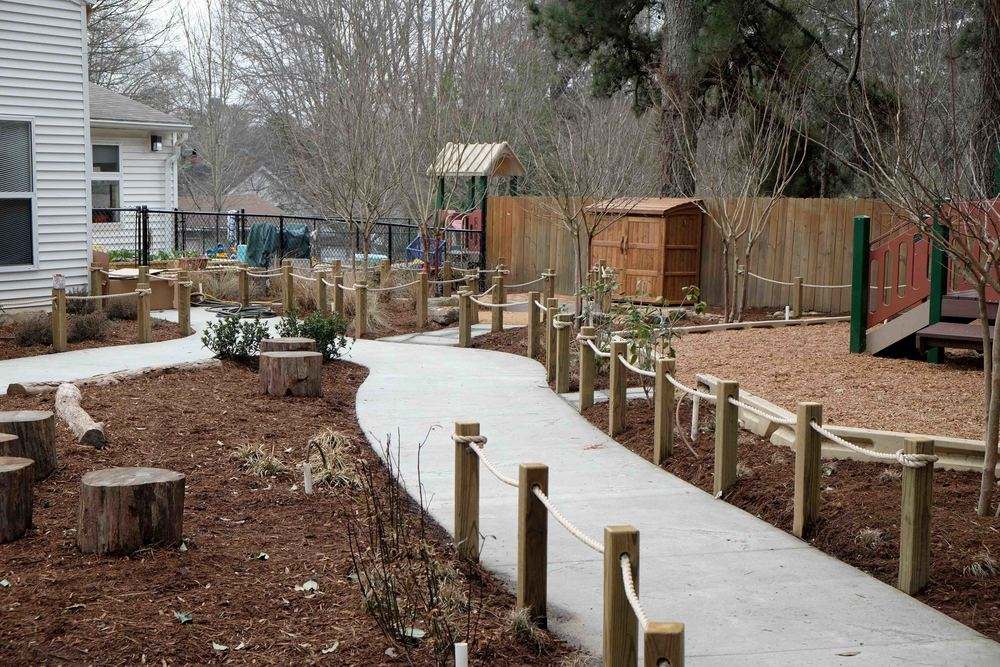 The play equipment on the right was existing but had much to broad use zones (that's where the safety mulch has to go). We trimmed those use zones down and made way for a path and a sitting/balancing area on the left.