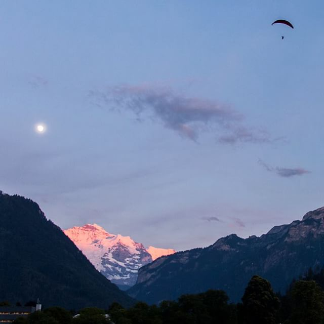 The Jungfrau, the moon, and a lone para glider at sunset in Interlaken #switzerland #mountains #dusk #travel