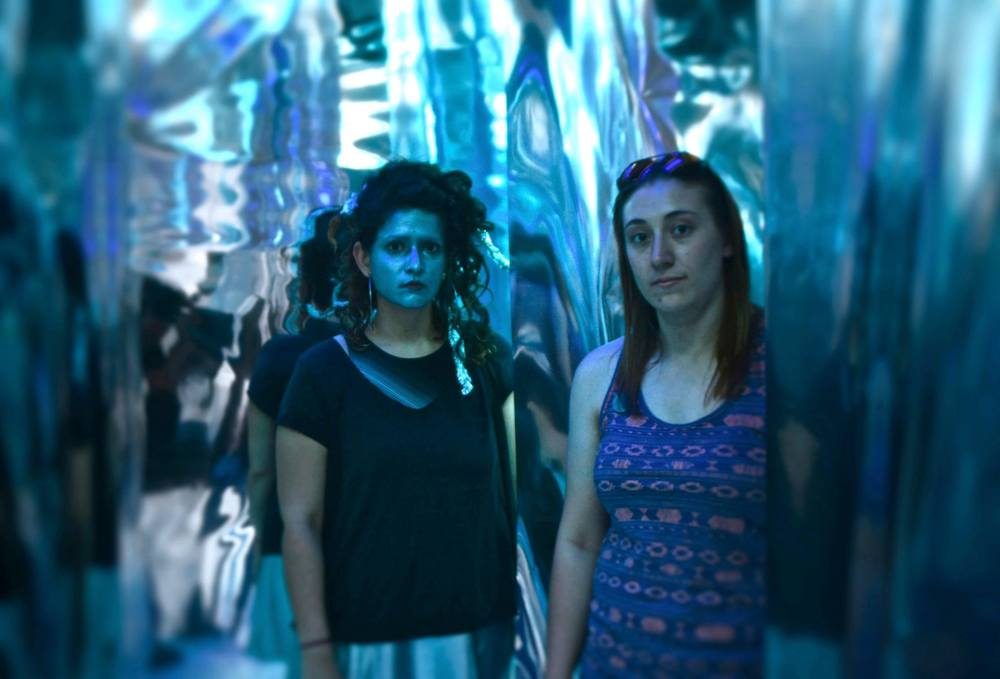 Paige Miller (right and Ashley Carrega transform the gallery one more time.  (Photo by Gary Reed)