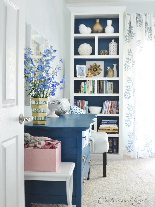 I love the combination of different sized vases, stacked books, and a pop of color on the back. Source:  www.centsationalstyle.com