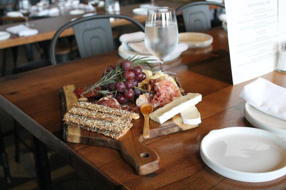 Charcuterie Board - Sliced Prosciutto de Parma, Alp's Sopressata, and Sweet Dried Sausage, French Brie, Aged Grana, Red Grapes, Truffle Honey, Crostini