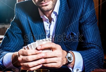 stock-photo--man-in-a-suit-player-sits-with-cards-in-a-hand-145026466.jpg