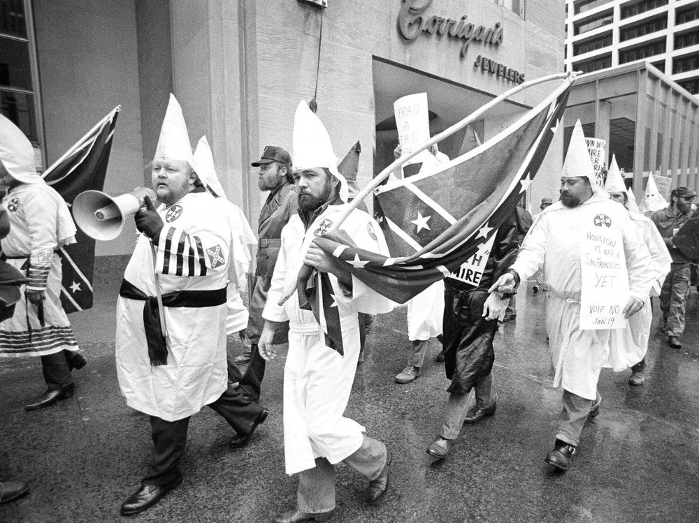 """The KKK demonstrating against LGBT people, in downtown Houston in the run-up to the January, 1985 ballot referendum. The signs read: """"Frag a fag"""" and """"Houston is not a San Francisco yet: Vote No Jan. 19."""""""