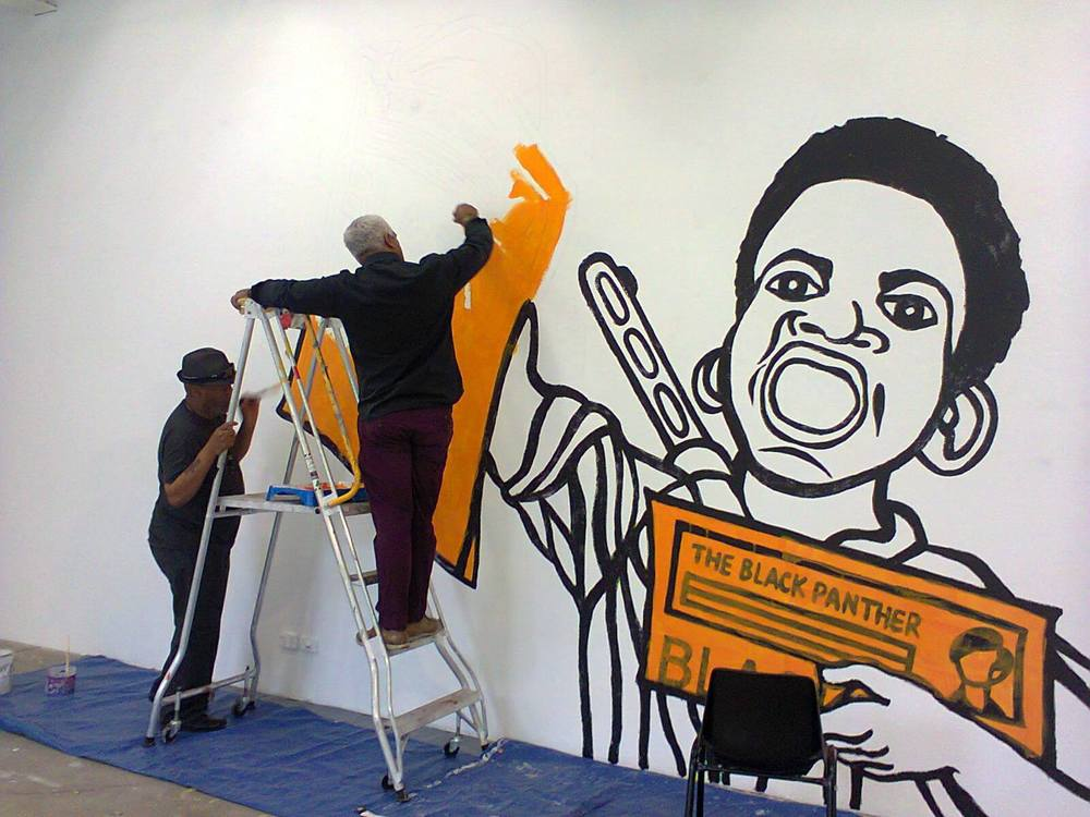 Emory Douglas installing/painting a poster recreation (2015)