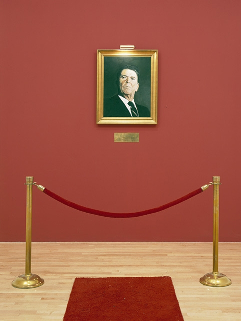 Hans Haacke Painting in Oils – Hommage to Marcel Broodthaers (detail), 1982 Painting in gold frame 35 1/2 x 29 inches Plus brass picture lamp, brass plaque with title, brass stanchions with velvet rope, red carpet runner, 54 feet