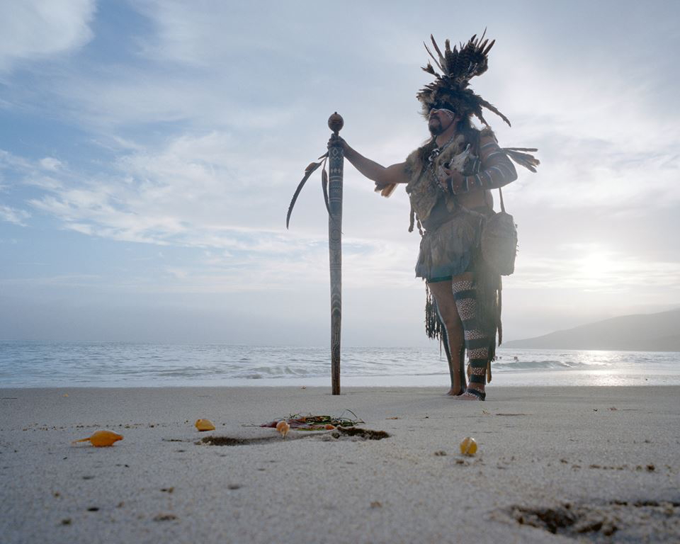 Mati Waiya, Chumash Ceremonial Elder in full regalia at Nicholas Canyon County Beach in front of Wishtoyo Chumash Village. Photo Credit: Jasmine Swope