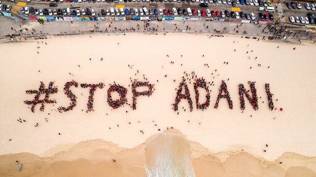 "The #StopAdani sign on Bondi Beach, NSW - Tricia Nugent rsm is in the ""N""."