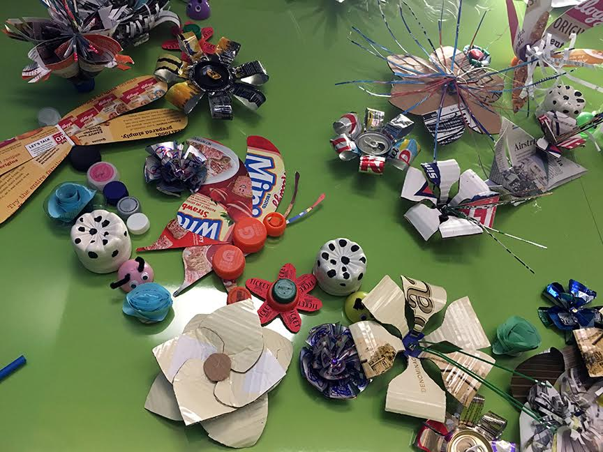 Materials included plastic bottles and lids, aluminum cans, cardboard, newspaper, junk mail catalogs, office waste paper, and printed food boxes. The variety of designs and methods for making the art objects was unlimited. Each item is individually attached to the wall with magnets.