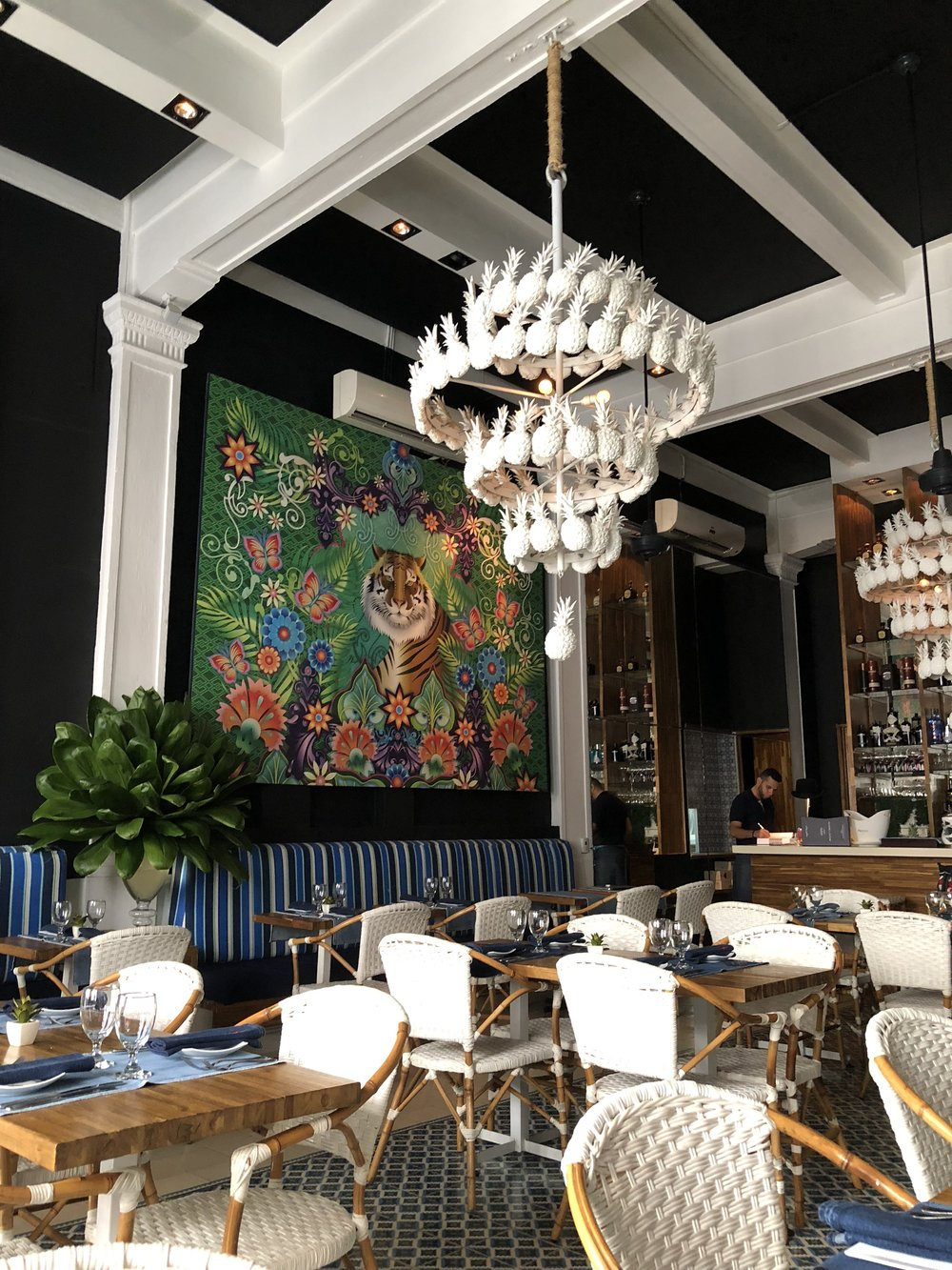 Maria - Colorful, elegant, and most importantly absolutely mouth-watering, the dishes at Maria will not disappoint. Designed by Maria Pinto, the stunning pineapple chandelier stands out against the mural of a tiger and sets the stage for woven white chairs that scream tropical chic.