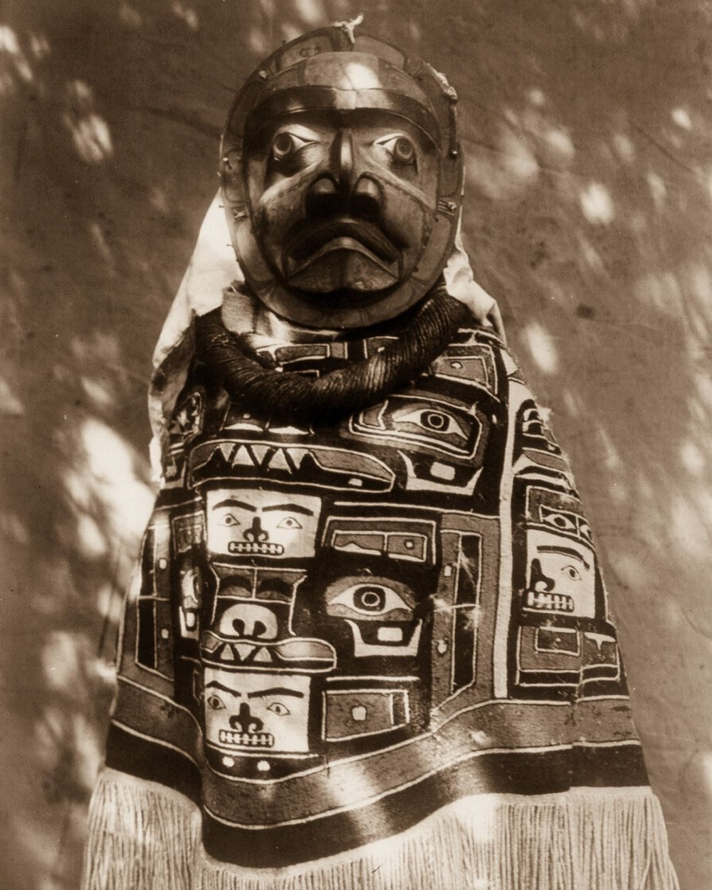 A Qagyuhl woman wears a fringed Chilkat blanket and a mask representing a deceased relative who had been a shaman , 1914.    ©EDWARD S. CURTIS/LIBRARY OF CONGRESS