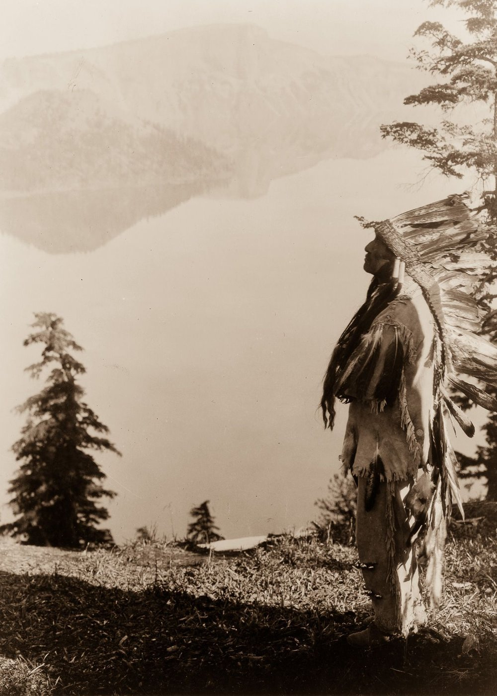 A Klamath chief stands on a hill above Crater Lake, Oregon,  1923.  ©EDWARD S. CURTIS/LIBRARY OF CONGRESS