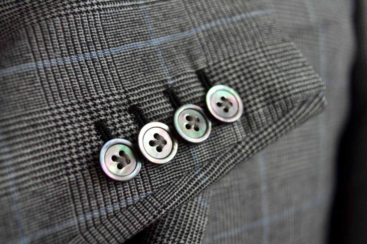 Hand sewn shell buttons and handmade button holes on a 1701 Bespoke Ariston gray and blue windowpane jacket.