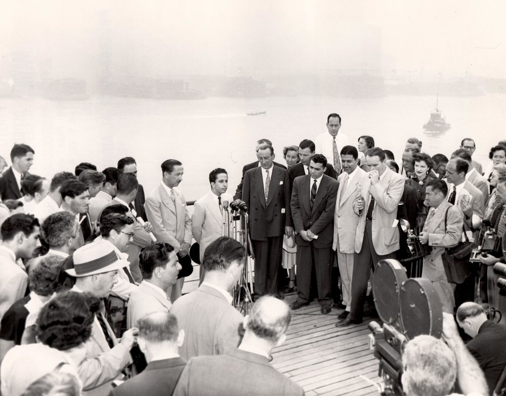 Aboard the RMS Queen Mary  King Faisal II of Iraq addressing the press; on the left is his uncle and regent, Abdul Ilah; to the right is John Coleman, Vice Chairman, Mayor's Reception Committee