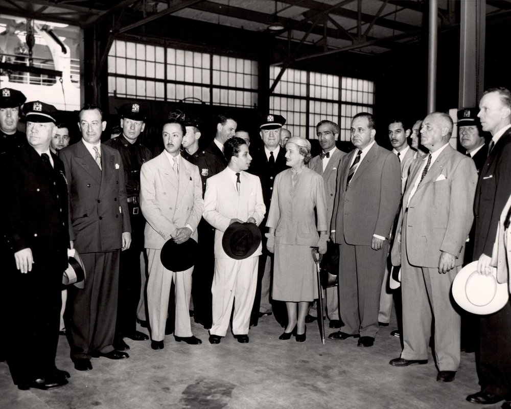 Disembarkation at Pier 90 King Faisal II (center) flanked by escorts; standing in front, second from the left is John Coleman, Vice Chairman of the Mayor's Reception Committee, with Prince-Regent Abdul Ilah between Coleman and Faisal