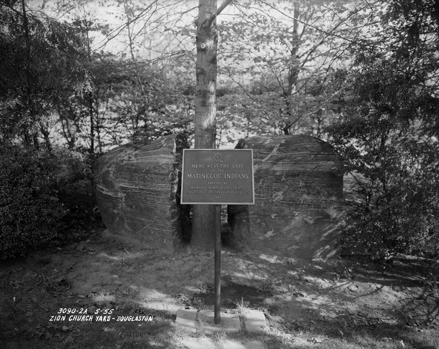 "Boulder split in half with carving ""Matinecoc"" and plaque reading ""Here Rest the Last of the Matinecoc Indians Erected by the Major Thomas Wickes Chapter Daughters of the American Revolution-1948."" Photo taken at Zion Church Yard, Douglaston, Queens, 1955. Borough President Queens collection, NYC Municipal Archives."