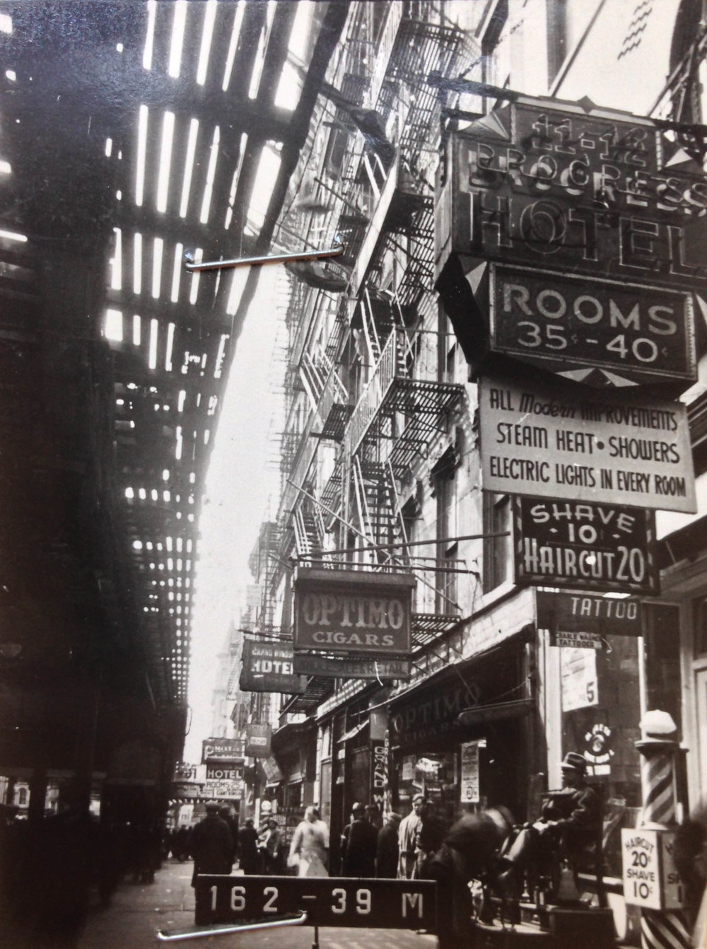 7 Chatham Square, Manhattan, circa 1940. The elevated train tracks, once part of the IRT Third Avenue Line, have been demolished. Prices on signs include 35 cents for a hotel rooms and a 10 cent barber shop shave. Department of Finance Collection, NYC Municipal Archives.