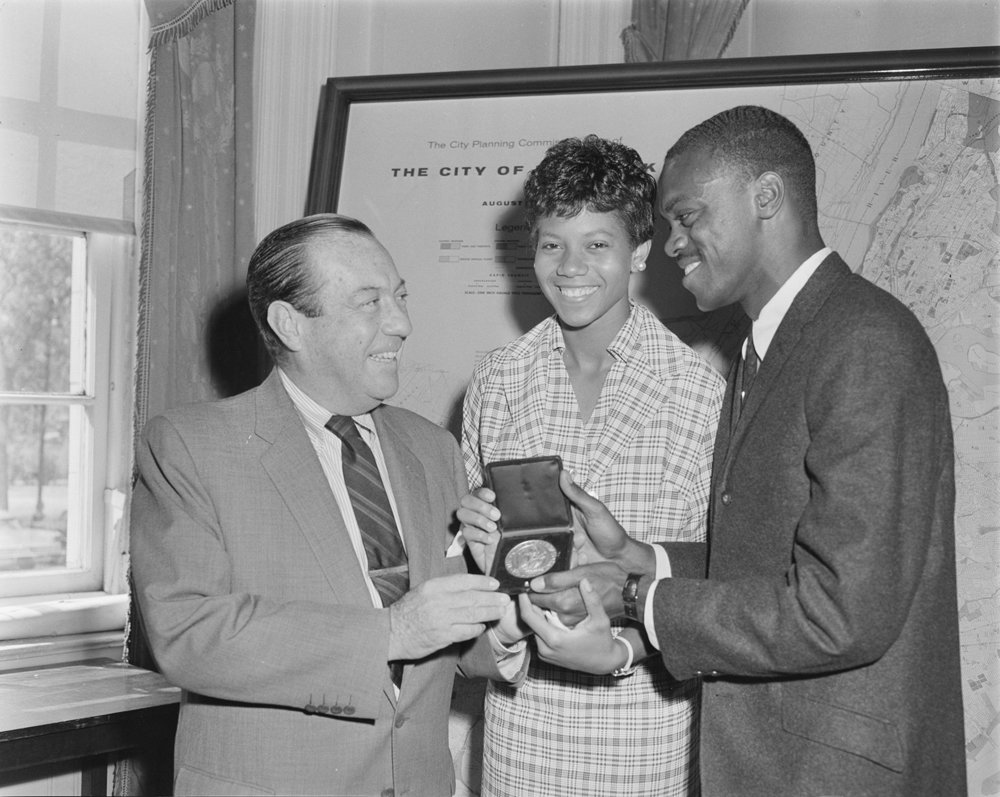 On September 26, 1960, at City Hall, Mayor Wagner presented special medallions to Wilma Rudolph, the first American woman to win three gold medals in track and field at a single Olympics, and to broad jump champion, Ralph Boston. Official Mayoral Photograph, NYC Municipal Archives.