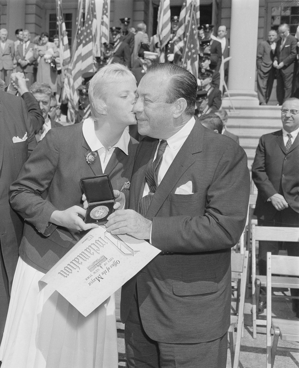 Lynn Burke, kissing Mayor Wagner as he presents her with a City medallion, September 1960. Official Mayoral Photographs, NYC Municipal Archives.