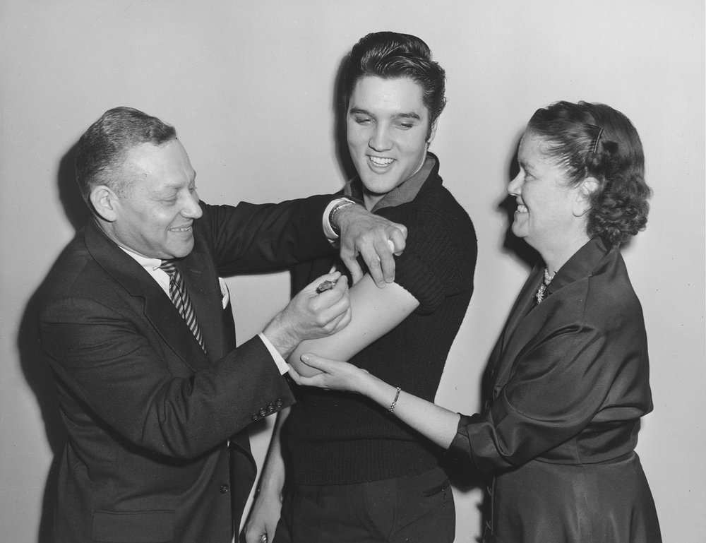 Elvis Presley receiving a polio shot in October 1956 from Assistant Commissioner Dr. Harold Fuerst. Commissioner Baumgartner holds Presley's arm while Fuerst administers the vaccine. Department of Health Collection, NYC Municipal Archives.