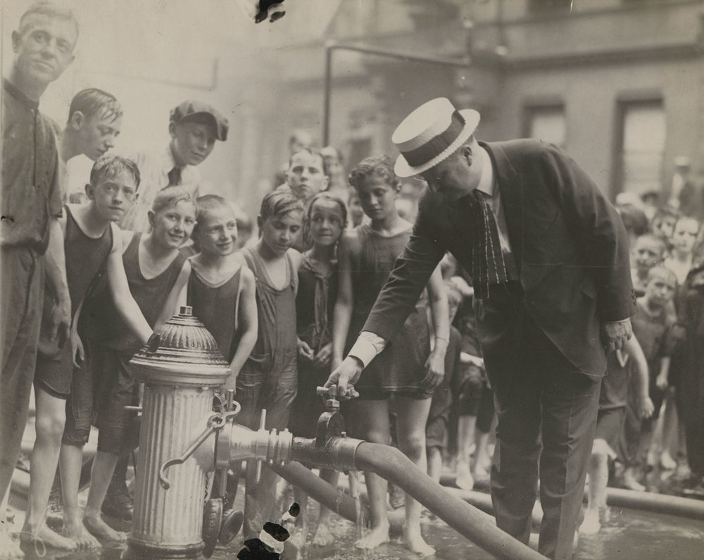 Mayor Hylan turning on the water for the first shower, West 47th Street near 8th Avenue, July 6, 1921. International Newsreel/Film Service, Inc. Mayor's Reception Committee, NYC Municipal Archives.