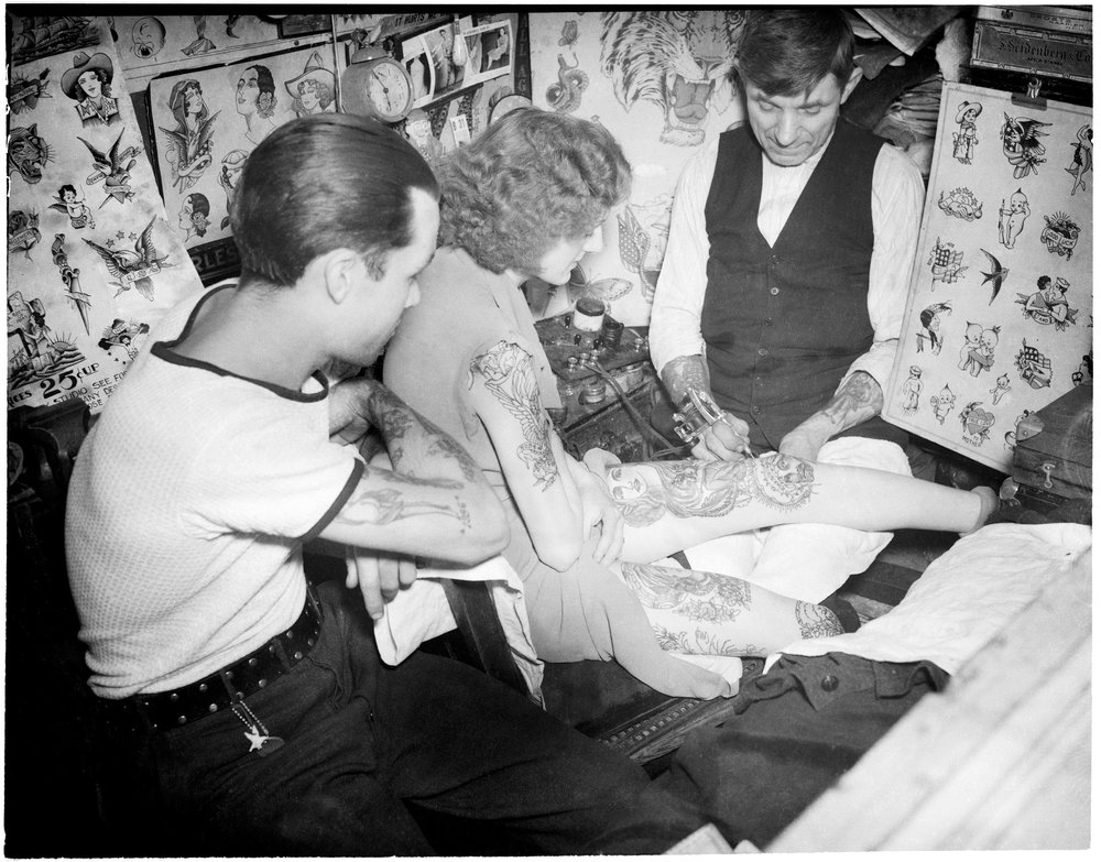Charlie Wagner tattooing a woman at his world-famous Bowery studio, 11 Chatham Square. Date: 1938. Photographer: Daniel Triestman. WPA-FWP Collection, NYC Municipal Archives.